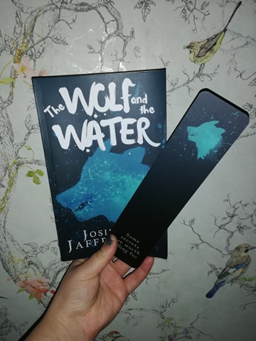 Cover image for 'The Wolf and the Water' by Josie Jaffrey, featuring a silhouette of a wolf on a dark navy background; the wolf is a cyan blue with water reflections.